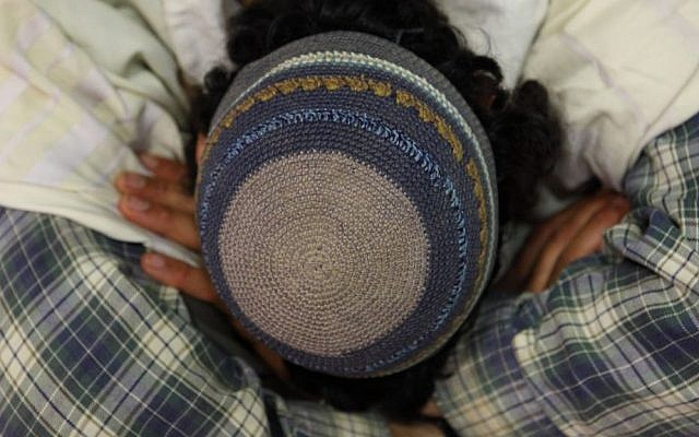An Orthodox Jewish man seen wearing a knitted kippah as he prays. (photo credit: Yaakov Naumi/Flash90)