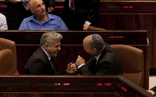 Laughing with a dictator? Naftali Bennett had some harsh words for his coalition partner Yair Lapid. Here the two laugh during a Knesset session in November 2013 (photo credit: Flash90)