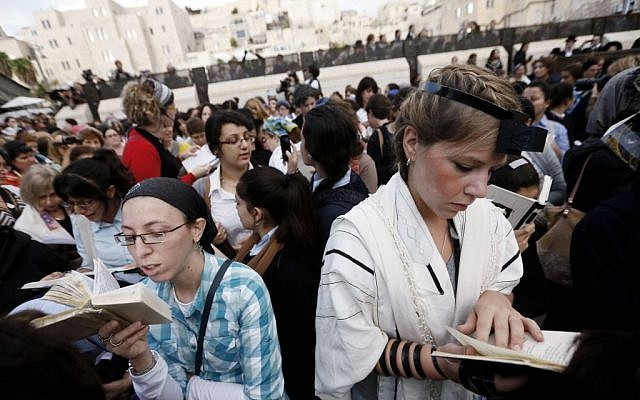 An Orthodox Jewish woman (left) prays alongside a young Jewish woman wearing tefillin at the Western Wall (photo credit: Miriam Alster/Flash90)
