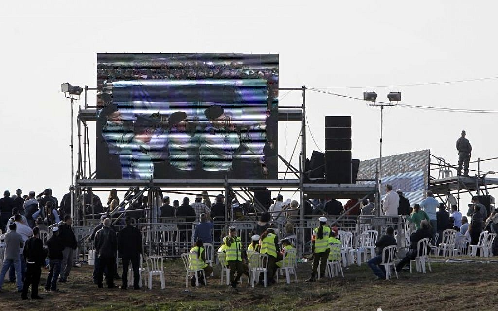 Spectators at the Sycamore Ranch watch a screen depicting IDF major generals bearing the coffin of former prime minister Ariel Sharon, Sunday, January 13, 2014 (photo credit: Miriam Alster/Flash90)