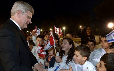 Canadian Prime Minister Stephen Harper is greeted by children waving Canadian and Israeli flags, during his official state visit to Israel, on Monday, January 20, 2014. (Haim Zach/GPO/Flash 90)