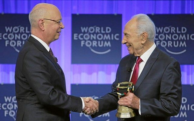 President Shimon Peres and Klaus Schwab the founder and Executive Chairman of the World Economic Forum shake hands as Peres holds an award from the WEF honoring him for his long-standing commitment to its mission, at the annual meeting of the WEF in Davos, January 24, 2014. (Photo credit: World Economic Forum/HANDOUT/Flash90)