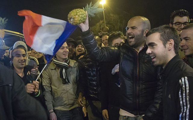"""People wave a French flag and hold a pineapple outside the Zenith arena where French comic Dieudonne's show was banned in Nantes, France, Thursday, Jan. 9, 2014. France's top administrative body turned the tables on Dieudonne, ruling in an urgent decision that his Thursday night show could not take place. The decision by the Council of State in Paris overturned a Nantes court ruling hours earlier that had annulled the ban the city had imposed on the show by Dieudonne M'Bala M'Bala. The comic was convicted last fall for using the word """"Shoananas,"""" a mash-up of the Hebrew word for Holocaust and the French word for pineapple. (photo credit: AP Photo/Michel Euler)"""
