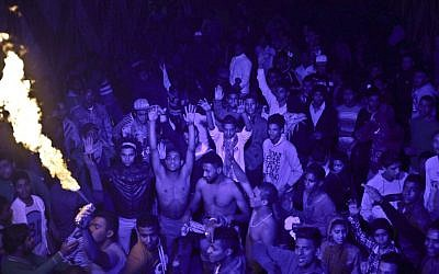 "In this Thursday, December 19, 2013 photo, Egyptian youths dance, to ""Mahraganat,"" Arabic for ""festivals,"" music, a rapid-fire electronic beat, mixed with hypnotic rhythms, during a bachelors party, in El-Marg, a suburb northeast of Cairo, Egypt. (photo credit: AP Photo/Nariman El-Mofty)"