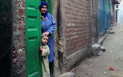 A Christian woman and her son stand in the doorway of their home in Dalga village of Minya, Egypt, Wednesday, January 15, 2014, on the second day of voting in the country's constitutional referendum (photo credit: AP/Roger Anis, El Shorouk Newspaper)
