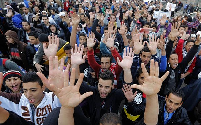 Egyptian protesters wave their hands as the chant anti-police and military slogans during a march towards the Egyptian Cabinet to commemorate the 2nd anniversary of the 2011 Cabinet clashes, on Kasr el-Nile bridge in Cairo, Egypt. December 16, 2013 (photo credit: AP Photo/Amr Nabil)