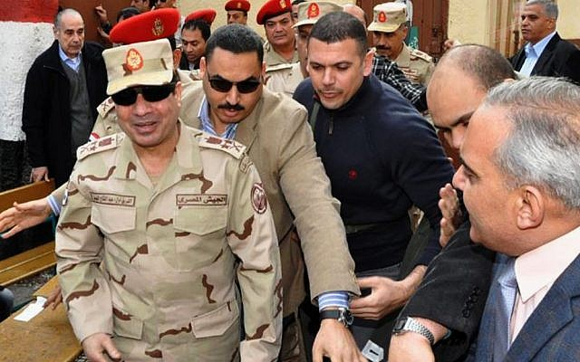 Abdel-Fattah el-Sissi, left, visits a polling site in the Heliopolis neighborhood of Cairo, Egypt, on the first day of voting in the constitutional referendum, on Jan 14, 2014 (photo credit: AP/Egyptian Defense Ministry via Facebook/File)