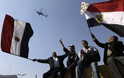 Egyptians wave national flags as they greet an army helicopter flying over Tahrir Square, the focal point of Egyptian uprising, in Cairo, Egypt, Saturday, Jan. 25, 2014. (AP Photo/Amr Nabil)