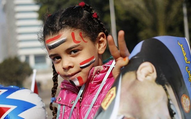 An Egyptian girl holds a poster of Egypt's Defense Minister, Gen. Abdel-Fattah el-Sissi, in Tahrir Square, the epicenter of the 2011 uprising, in Cairo, Egypt, Saturday, Jan. 25, 2014. Egyptian riot police have fired tear gas to disperse hundreds of supporters of ousted Islamist President Mohammed Morsi protesting as the country marks the third anniversary of the 2011 uprising, as supporters of the military gathered in rival rallies in other parts of the capital. (AP Photo/Hassan Ammar)