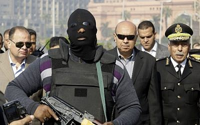 An Egyptian masked policeman guards Cairo's state security chief, Osama al-Saghir, third right, as he visits Tahrir Square, the epicenter of the 2011 uprising, in Cairo, Egypt, Saturday, Jan. 25, 2014. (AP Photo/Amr Nabil)