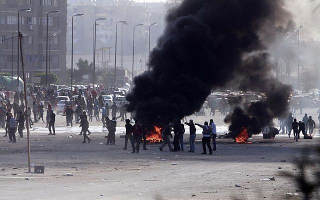 Supporters of ousted President Mohammed Morsi damage an area on a street as they protest against the government in Cairo's Nasr City district, Egypt, Friday, Jan, 24, 2014. (photo credit: AP/El Shorouk newspaper, Sabry Khaled)