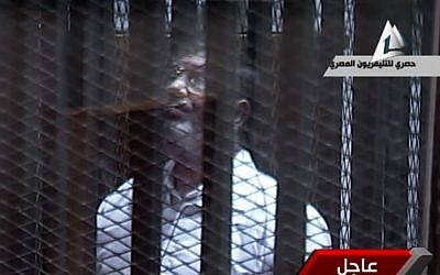 Toppled President Mohammed Morsi stands inside a glass-encased metal cage in a courtroom in Cairo, Tuesday, Jan. 28. 2014.  (photo credit: AP/Egyptian State TV)