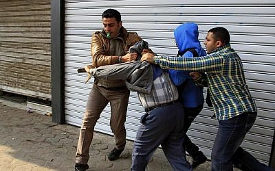 Egyptian plainclothes policemen arrest a supporter of ousted Islamist president Mohammed Morsi during clashes in Cairo, Egypt, on Friday (photo credit: AP/Ahmed Abd El Latif/El Shorouk newspaper)