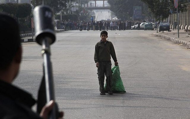 A boy looks at Egypt's security forces as they try to disperse supporters of ousted President Mohammed Morsi in Cairo, Egypt, Friday, Jan. 17, 2014. (photo credit: AP/Aly Hazzaa)