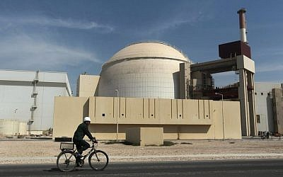 A worker rides a bicycle in front of the reactor building of the Bushehr nuclear power plant, just outside the southern city of Bushehr, Iran,  Oct. 26, 2010. (Photo credit: AP/Mehr News Agency, Majid Asgaripour)