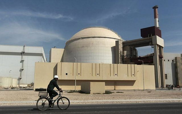 A worker rides a bicycle in front of the reactor building of the Bushehr nuclear power plant, just outside the southern city of Bushehr, Iran,  Oct. 26, 2010. (AP/Mehr News Agency, Majid Asgaripour)