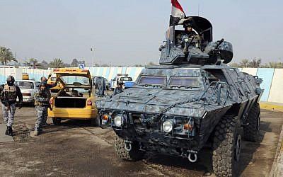 Iraqi federal policemen search a car at a checkpoint in Baghdad, Iraq, Tuesday, Dec. 31, 2013. (AP Photo/Karim Kadim)