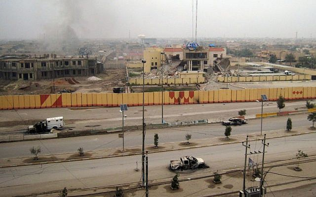 An empty street shows burned vehicles, as buildings including a provincial government building (center, in the background), are seen damaged in Fallujah, 40 miles (65 kilometers) west of Baghdad, Iraq, on January 3, 2014. (photo credit: AP)