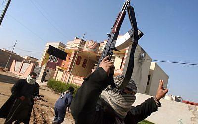Gunmen patrol in Fallujah, 40 miles (65 kilometers) west of Baghdad, Iraq, on January 9, 2014. (photo credit: AP)