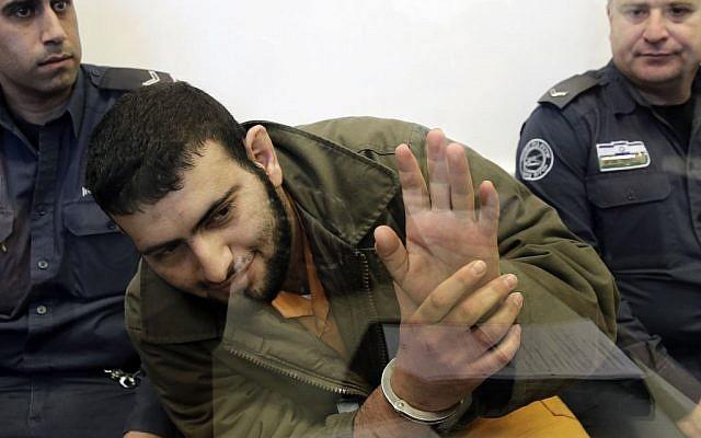 Palestinian Eyad Abu, shot through a glass partition, waves to his family in the court of Ashkelon, Israel, Sunday, Jan. 26, 2014. (photo credit: AP/Tsafrir Abayov)