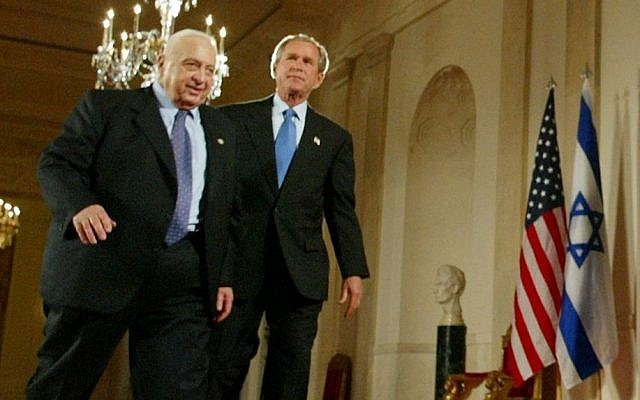 George W. Bush, right, and Ariel Sharon, left, walk together at the end of a joint press conference in the Cross Hall of the White House in Washington in April, 2004. (photo credit: AP/Pablo Martinez Monsivais, File)