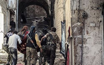 This file photo from 2012 shows a group of Free Syrian Army fighters carrying a wounded comrade to cover in the town of Harem, Syria. (photo credit: AP Photo/Mustafa Karali, File)