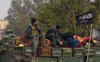 This January 2013 citizen journalism image shows rebels from al-Qaeda affiliated Jabhat al-Nusra, as they sit on a truck full of ammunition, at Taftanaz air base, that was captured by the rebels, in Idlib province, northern Syria. The photo was authenticated based on its contents and other AP reporting. (photo credit: AP Photo/Edlib News Network, ENN, File)