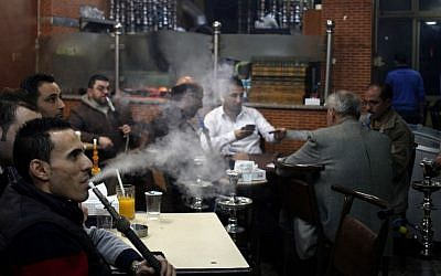 In this Thursday, Jan. 23, 2014 photo, customers smoke water pipes at a coffee shop in Amman, Jordan. In Jordan, a country where smoking is so popular that motorists can be seen puffing away on miniature water pipes in traffic, the kingdom's government now wants to enforce a Western-style smoking ban in restaurants, cafes and other public places. (photo credit: AP/Mohammad Hannon)