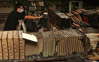 A Lebanese activist removes burned books, at the Saeh (Tourist) Library which was set on fire by masked men, in the northern city of Tripoli, Lebanon, January 2014. (AP Photo/Hussein Malla)
