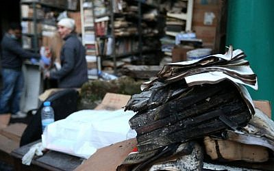Charred books in the backyard of the Saeh (Tourist) Library, which was set on fire by masked men in the northern city of Tripoli, Lebanon, Sunday, January 5, 2014. (photo credit: AP/Hussein Malla)