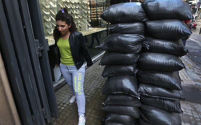 A Lebanese girl passes next to sand barriers in front of a jewelry shop, in a Shiite neighborhood in Beirut, Lebanon, on January 28, 2014. (photo credit: AP/Hussein Malla)