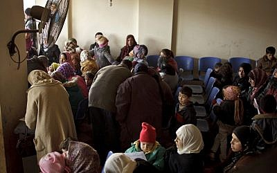 Syrians wait for their appointments at the UN refugee agency's registration center in Zahleh, in Lebanon's Bekaa Valley, Dec. 18, 2013 (photo credit: AP/Maya Alleruzzo)