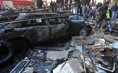 A Lebanese army soldier walks through the site of a car bombing in the southern suburb of Beirut, Lebanon, Tuesday, Jan. 21, 2014. (Photo credit: AP/Hussein Malla)