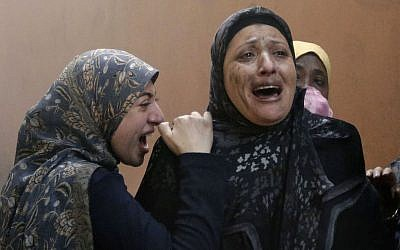 Lebanese women who left their destroyed home cry out after a car bomb explosion hit a stronghold of the Shiite Hezbollah group in a southern suburb of Beirut, Lebanon, on Thursday. (photo credit: AP/Hussein Malla)