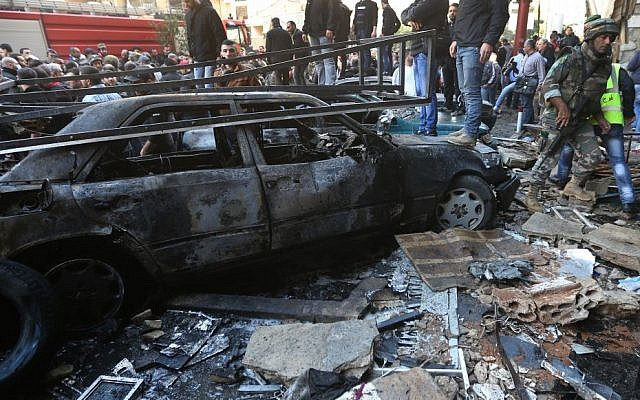 A Lebanese army soldier walks through the site of a car bombing in a southern suburb of Beirut, Lebanon, Tuesday (photo credit: AP/Hussein Malla)