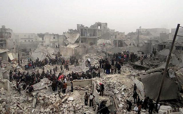 People searching through the debris of destroyed buildings in the aftermath of a strike by Syrian government forces, in the neighborhood of Jabal Bedro, Aleppo, Syria, February 19, 2013. (photo credit: AP/Aleppo Media Center AMC)