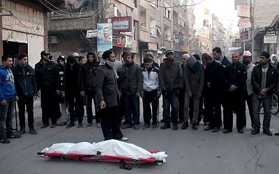 This undated activist photo provided by the group Palestinians of Syria shows mourners praying next to the body of a man who died of hunger-related illness in the Palestinian neighborhood of Yarmouk in Damascus, Syria.(photo credit: AP/Palestinians of Syria)