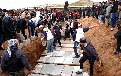 Syrian citizens bury in a mass grave the bodies of victims who were killed Thursday by a car bomb in Hama province, Syria, on Friday (photo credit: AP/SANA)