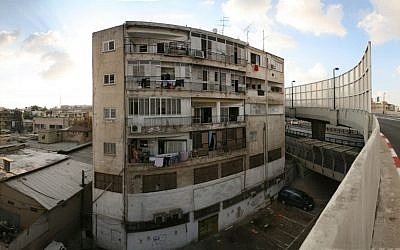 Boarding platforms at the Central Bus Station run past a dilapidated apartment building. (photo credit: Wikimedia/Roi Boshi)