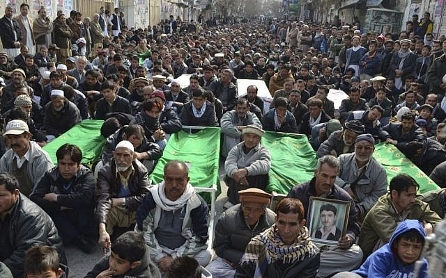Relatives and mourners of Shiite pilgrims who were killed on Tuesday in a bus bombing, protest sitting next to their bodies, in Quetta, Pakistan, on Wednesday (photo credit: AP/Arshad Butt)