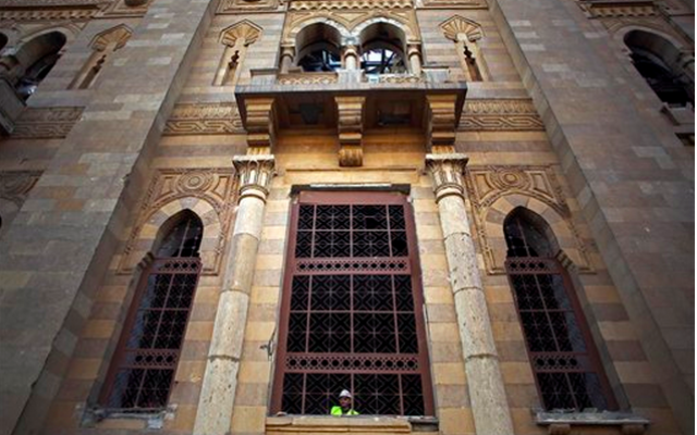 An Egyptian worker peers from the window of the damaged Museum of Islamic Art after an explosion at the Egyptian police headquarters in downtown Cairo, Friday, January 24. (photo credit: AP Photo/Khalil Hamra)