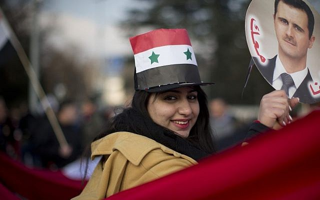 A Syrian demonstrator holds up a picture of Syrian President Bashar Assad as she shouts pro-government slogans during a demonstration outside the United Nations headquarters in Geneva, Switzerland, Friday (photo credit: AP/Anja Niedringhaus)