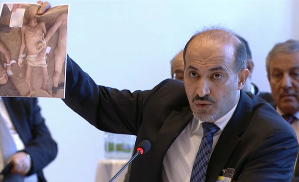 Amhad al-Jarba, the head of Syria's Western-backed Syrian National Coalition, holding up an image of alleged torture victims, during Syrian peace talks in Montreux, Switzerland, Jan. 22, 2014 (photo credit: AP)