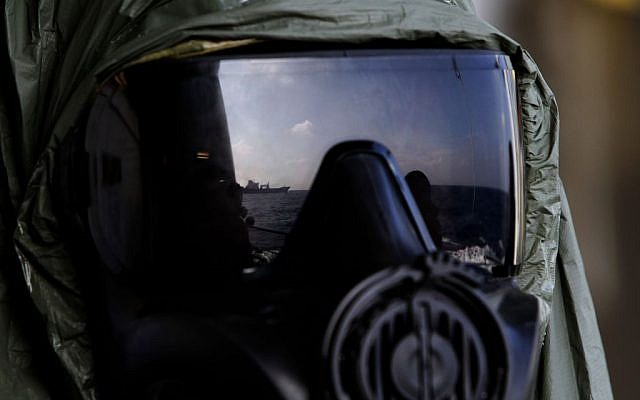 A crew member of the Danish warship Esbern Snare wears a protective mask during emergency drills ahead of their mission to the Syrian port of Latakia, where they will pick up more than 1,000 tons of chemical agents. (photo credit: AP Photo/Petros Karadjias)