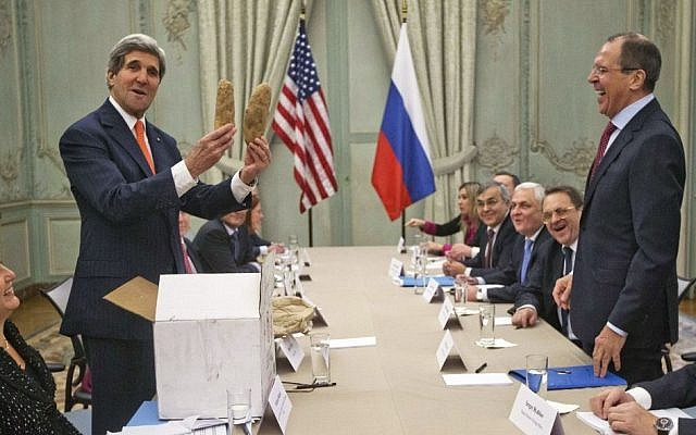 US Secretary of State John Kerry holds up a pair of Idaho potatoes as a gift for Russian Foreign Minister Sergey Lavrov, standing right, at the start of their meeting at the US Ambassador's residence in Paris, France, Monday. (AP Photo/Pablo Martinez Monsivais)