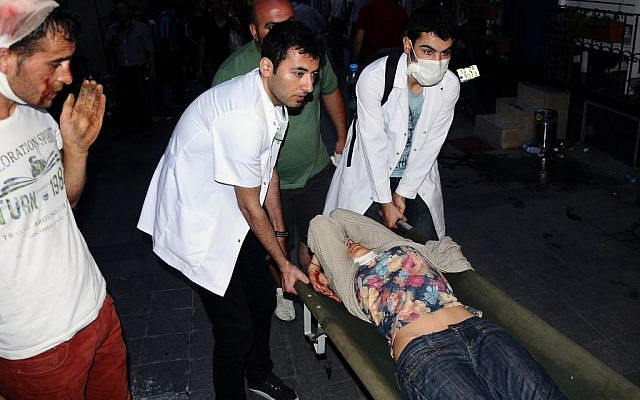 Volunteer Turkish doctors help a demonstrator overcome from pepper gas during clashes with riot police near Taksim Square in Istanbul, Turkey, May 31, 2013.  (photo credit: AP/Emrah Gurel)