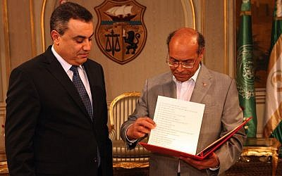 Interim Prime Minister, Mehdi Jomaa, left, presents the list of the members of his government to Tunisian President Moncef Marzouki during the new government presentation ceremony at the presidential palace in Carthage near Tunis, Sunday, Jan. 26, 2014. Tunisia's interim prime minister announced on Sunday his new government following a 24-hour delay over the post of interior minister. Mehdi Jomaa, the interim prime minister, had been working since Jan. 10 to form a government of technocrats to guide the country to new elections after a political crisis that began last year between Islamists and the opposition following the assassination of an opposition politician. (photo credit: AP/Hassene Dridi)