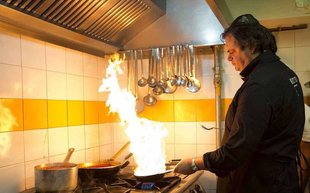 Ba'Ghetto restaurant co-owner and chef Ilan Dabush cooks in Rome, Monday, Jan. 20, 2014. For just one day, the kitchen of the Vatican hotel where Pope Francis lives went kosher, with Rabbi Jaakov Spizzichino overseeing the scrupulous cleaning of countertops, boiling of utensils and heating of the oven necessary to render it fit for cooking under Jewish dietary laws.  (photo credit: AP/Alessandra Tarantino)