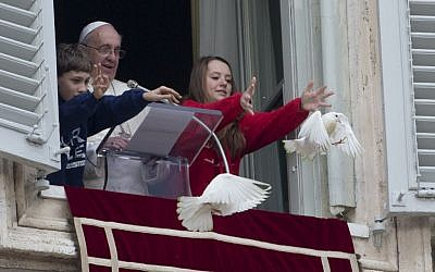 Pope Francis looks on as two children free doves during the Angelus prayer he celebrated from the window of his studio overlooking St. Peter's Square, at the Vatican, Sunday, Jan. 26, 2014. (photo credit: AP/Gregorio Borgia)