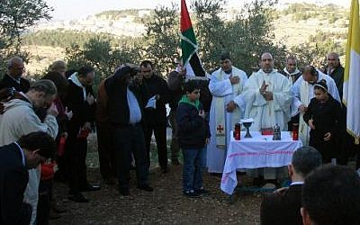 The Beit Jala' Roman Catholic parish priest leads a mass to protest against Israel's decision to build a new section of the security fence through the Cremisan valley on January 24, 2014 (photo credit: Musa al-Shaer/AFP)